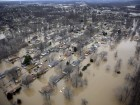 In this aerial photo, houses are surrounded by floodwater, Thursday, Dec. 31, 2015, in Arnold, Mo. Surging Midwestern rivers forced hundreds of evacuations, threatened dozens of levees and brought transportation by car, boat or train to a virtual standstill Thursday in the St. Louis area. (AP Photo/Jeff Roberson)