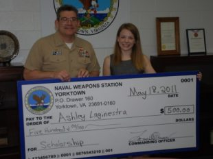 Captain Lowell Crow, Commanding Officer, Naval Weapons Station (WPNSTA) Yorktown, presents Ashley Laginestra with $500 as the 2011 recipient of the Nick and Mary Mathew's Scholarship. Laginestra, the daughter of MMCS Jody Reynolds of the Naval Submarine Torpedo Facility, is a senior at Bruton High School and will be attending Liberty University in the fall. This TRICARE change will affect young adult children of military personnel. (U.S. Navy photo)