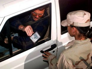 Airman Mary Ann Hubany, a security forces specialist, checks a driver's military identification card for positive identification before allowing the vehicle to enter the U.S. military compound at an operating base in Southwest Asia on February 23, 1998. (DoD photo)