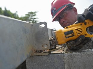 Pennsylvania National Guard Senior Master Sgt. Ronald Hinsey, 201st Rapid Engineer Deployable Heavy Operational repair Squadron Engineers structures superintendent, grinds a mounting plate to size for a new medical clinic. Photo by Senior Airman Dillon Davis