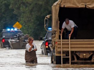 Jeff Robinson lowers a ladder from a Louisiana National Guard truck as his wife wades through flood waters from the Natalbany River near their home in Baptist, Louisiana. AP Photo/Rogelio V. Solis