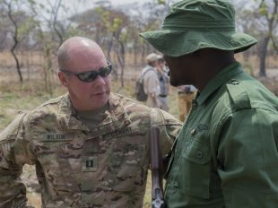 U.S. Army Capt. Michael Wilson, 403rd Civil Affairs Battalion team leader, speaks with a Tanzanian Ranger after a demonstration of capabilities Aug 24, 2016, at Rungwa Game Reserve, Tanzania. Members form the 403rd Civil Affairs Battalion, a component of Joint Task Force - Horn of Africa, and North Carolina Army National Guard, taught the rangers techniques to increase their skills in small unit tactics, first aid, gathering intelligence and other field crafts. The soldiers were training the rangers in how to combat poachers on the reserve. Poaching and trafficking in wildlife has become a source of revenue for violent extremist organizations on the continent. (U.S. Air Force photo by Staff Sgt. Eric Summers Jr./Released) Download full-resolution