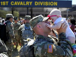 Pfc. Shane Mowery holds his daughter Savannah on Cooper Field after returning from a deployment in Korea, Tuesday, Oct. 11, 2016.