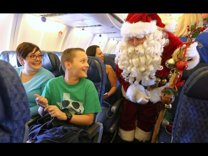 Brandy Jackson and her son, Michael Strom, talk with Santa on a plane as they join American Airline's 11th annual Snowball Express at the Salt Lake City International Airport on Sunday, Dec. 11, 2016, an event for children of fallen military heroes. (Photo: Scott G Winterton, Deseret News