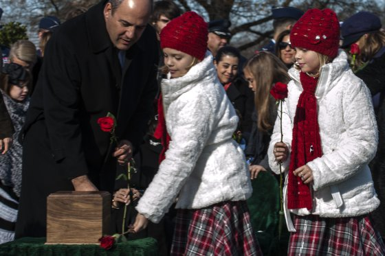 Aspen and Annalise Gilbert Ravella, lay flowers next to their father's remains, Maj. Troy Gilbert, during his remembrance funeral at Arlington Cemetery, Dec. 11, 2013. (U.S. Air Force photo by Staff Sgt. Carlin Leslie)