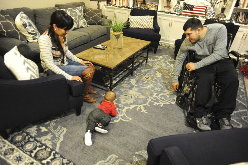 Photos by Kelby Wingert, Sentinel Sta Mara Nesmith and Sgt. Carlos Nesmith, WTU, watch their 9-month-old son, Carlos III, crawl around the Fort Hood Fisher House's living room. Staying in the Fisher House while Sgt. Nesmith goes through physical therapy and rehabilitation for a spinal cord injury gives the Family a sense of comfort and home that they wouldn't have staying in a hotel room.
