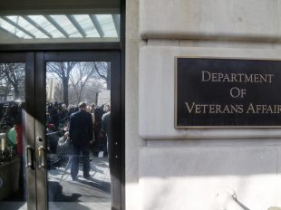 Department of Veterans Affairs Secretary Robert McDonald (reflected in doors, facing reporters) speaks outside VA headquarters in Washington, D.C. in 2015. Photo by Jonathan Ernst/Reuters