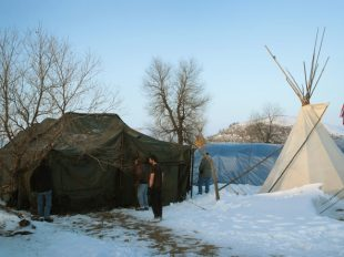 CANNON BALL, ND - DECEMBER 03:  Military veterans build a tent at Oceti Sakowin Camp on the edge of the Standing Rock Sioux Reservation on December 3, 2016 outside Cannon Ball, North Dakota. As many as 2,000 veterans are expected at the camp this weekend to participate in non-violent protests against the construction of the Dakota Access Pipeline. Native Americans and activists from around the country have been gathering at the camp for several months trying to halt the construction of the pipeline. The proposed 1,172-mile-long pipeline would transport oil from the North Dakota Bakken region through South Dakota, Iowa and into Illinois.  (Photo by Scott Olson/Getty Images)
