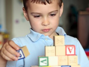 Autistic boy building with blocks