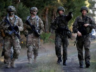 Poland's 6th Airborne Brigade soldiers (R) walk with U.S. 82nd Airborne Division soldiers during the NATO allies' Anakonda 16 exercise near Torun, Poland, June 7, 2016. REUTERS/Kacper Pempel/File Photo - RTX2JWU7