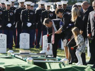 The family of Marine 1st Lt. Travis L. Manion drops roses into his gravesite during the reinternment ceremony for Manion, of Doylestown, Penn., at Arlington National Cemetery, in Arlington, Va. on Friday, Oct. 1, 2010