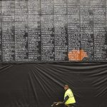 A man walks past the Vietnam veterans mural that was covered with plastic after it was vandalized just before Memorial Day. (Al Seib / Los Angeles Times)