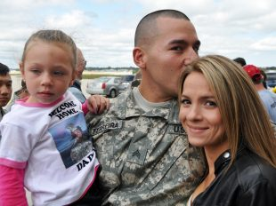 Sgt. Johnny Ferreira of the Wisconsin Army National Guard's 32nd Military Police Company greets his daughter Leia and fiancee Candace during a welcome home ceremony Thursday (Sept. 27) at the 128th Air Refueling Wing in Milwaukee. Gov. Scott Walker, Maj. Gen. Don Dunbar, adjutant general of Wisconsin, family and friends greeted approximately 125 Soldiers from the Milwaukee-based Headquarters Company, 157th Maneuver Enhancement Brigade (MEB) and the 32nd MP Company after the Soldiers completed a year-long deployment in support of NATO peace-keeping missions in Kosovo. The Soldiers largely made up the brigade headquarters for Multinational Battle Group East, also referred to as Task Force Falcon, and supported the Kosovo Force mission by maintaining a safe and secure environment and freedom of movement in Kosovo. Wisconsin National Guard photo by Vaughn R. Larson