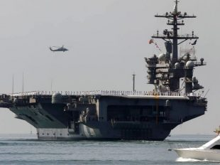 FILE - In this Aug. 22, 2014 file photo, the aircraft carrier USS Carl Vinson sails out of San Diego Harbor leaving for a nine month deployment in San Diego.  (AP)