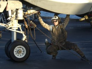 "020125-N-2722F-051 At sea aboard USS John C. Stennis (CVN 74) Jan. 25, 2002 -- Aviation Electronics Technician 3rd Class Delilah Clymer checks the landing gear of an F-14A ""Tomcat"" on the flight deck of USS John C. Stennis (CVN 74).  Clymer is assigned to the ""Checkmates"" of Fighter Squadron Two One One (VF-211), deployed with John C. Stennis in support of Operation Enduring Freedom.  U.S. Navy photo by Photographer's Mate 2nd Class James A. Farrally.  (RELEASED)"