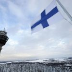 The Finnish flag flies over a wintry landscape in the east of the country Getty