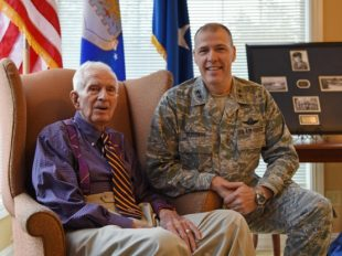 U.S. Air Force Maj. Gen. Thomas Bussiere, 8th Air Force commander, presents 93-year-old World War II veteran Raymond Odom with his dog tags at Arbor Rose Assisted Living Facility in Farmerville, Louisiana.