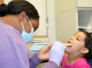 Capt. Adrienne Rembert, DDS conducts an oral screening for Reilli Wade, an Arnn Elementary first-grader, Feb. 20, during a preventative health visit for National Children's Dental Awareness Month. (U.S. Army / Candateshia Pafford)
