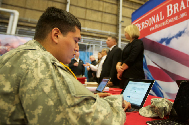 A military specialist works on his resume during a job fair in Washington state.
