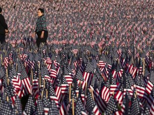 A 74-year-old veteran faces criminal charges after displaying American flags and taking photos at a veterans park in Los Angeles. (Steven Senne/The Associated Press)
