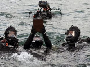 In this Saturday, April 15, 2017 photo released by Pacific Historic Parks, divers take the urn containing the remains of Raymond Haerry underwater to his final resting place within the sunken hull of the USS Arizona during a ceremony at the USS Arizona Memorial in Honolulu.  (Elaine Simon/Pacific Historic Parks via AP)