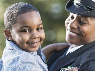 An African American woman wearing a naval officer uniform holding her 5 year old son. The focus is on the little boy who is smiling and looking at the camera.