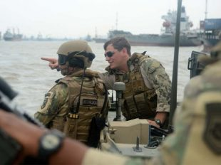 Lt. David Nartker, right talks with an Indonesian Naval Special Forces member while practicing small boat tactics during Cooperation Afloat Readiness and Training Indonesia 2015. (U.S. Navy photo/Joshua Scott)