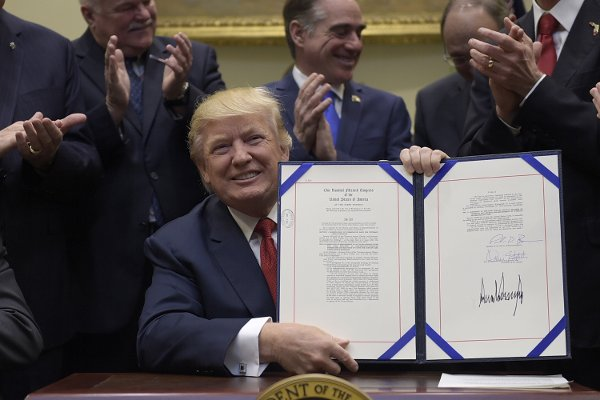 President Trump hold up the Veterans Choice Program Extension and Improvement Act that he signed, Wednesday, April 19, 2017, in the Roosevelt Room of the White House in Washington. (AP Photo/Susan Walsh)