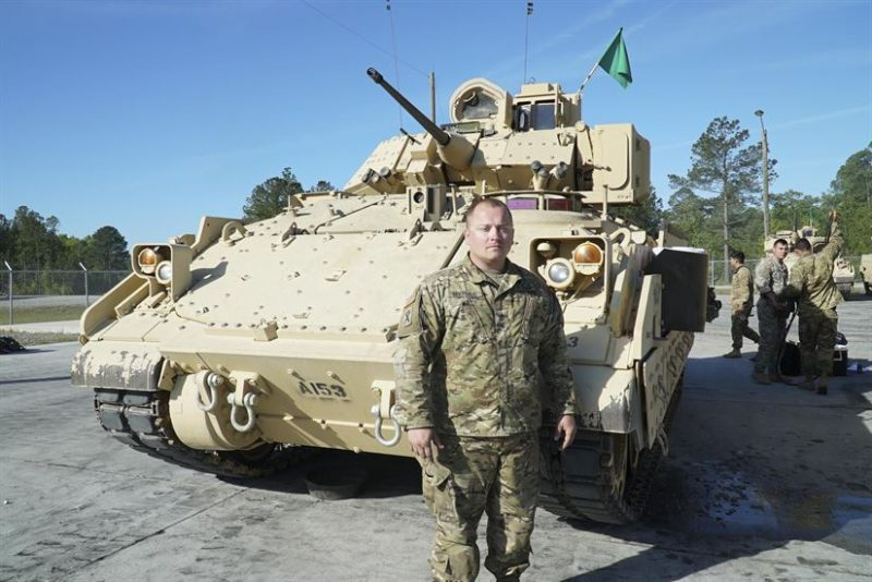 Army Staff Sgt. Jeffrey Hoffhaus, Company A, 4-118th Combined Arms Battalion, 218th Maneuver Enhancement Brigade, South Carolina National Guard, poses next to his M2 Bradley Infantry Fighting Vehicle during an annual training event at Fort Stewart, Georgia, April 10, 2017. Army photo by Capt. Brian Hare