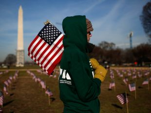 """WASHINGTON, DC - MARCH 27:  Iraq war veteran Sara Poquette helps set up 1,892 American flags on the National Mall March 27, 2014 in Washington, DC. The Iraq and Afghanistan Veterans of America installed the flags to represent the 1,892 veterans and service members who committed suicide this year as part of the """"We've Got Your Back: IAVA's Campaign to Combat Suicide.""""  (Photo by Win McNamee/Getty Images)"""