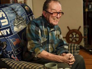 In this November 2014 photo, Lawrence J. Reilly Sr., a U.S. Navy veteran of World War ll and the Vietnam War, sits in the living room of his home in Syracuse, N.Y. He and his 20-year-old son Lawrence J. Reilly