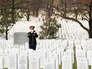 A bugler plays Taps at the funeral of Army Staff Sgt. Kevin McEnroe at Arlington National Cemetery on Dec. 5, 2016. McEnroe, 30, was one of three U.S. servicemembers killed while entering a Jordanian military base in November. C.J. LIN/STARS AND STRIPES